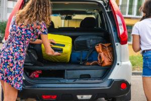 Женщина загружает багаж в автомобиль