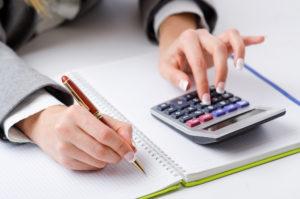Руки держат карандаш и калькулятор