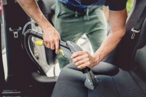 Человек вылесосит салон автомобиля