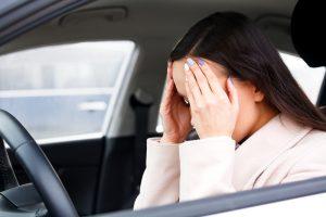 Девушка держится за голову в автомобиле